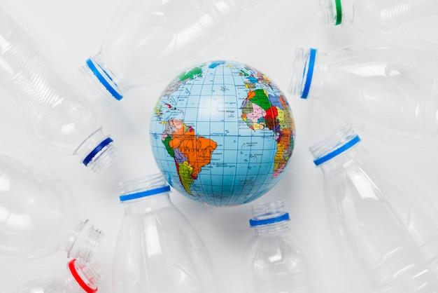 Globo de la tierra rodeado de botellas de plástico en mesa gris