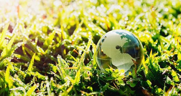 Globo de vidrio sobre césped con sol. concepto de medio ambiente