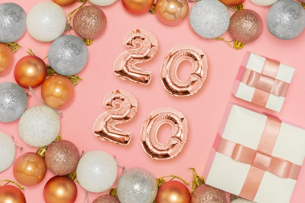 Globos 2020 composición de año nuevo. concepto de decoración elegante, brillantes adornos navideños, cajas de regalo, en rosa