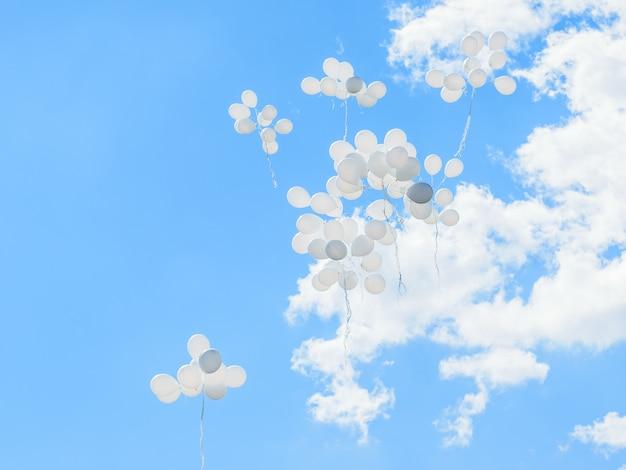 Globos blancos vuelan alto hacia el cielo con nubes