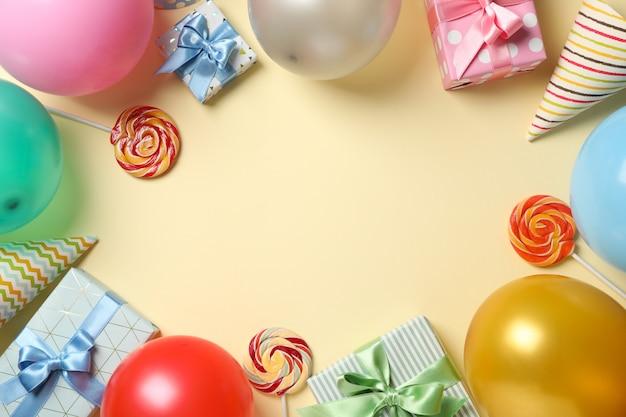 Globos, cajas de regalo, piruletas y sombreros de cumpleaños sobre fondo de color, espacio para texto