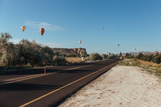 Los globos de la carretera de capadocia se elevan por encima de ella