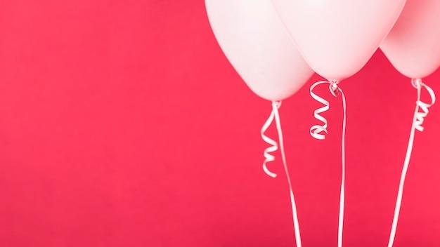 Globos de color rosa sobre fondo rojo con espacio de copia