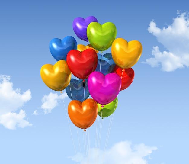 Globos coloreados de la forma del corazón que flotan en un cielo azul