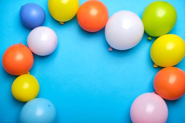 Globos de colores en la vista superior de la mesa azul. fondo festivo o de fiesta. estilo plano. copie el espacio para el texto. tarjeta de felicitación de cumpleaños.