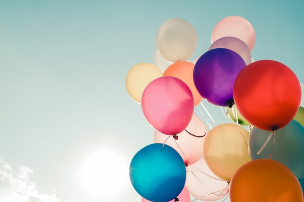 Globos coloridos que vuelan en cielo con un efecto retro del filtro de la vendimia. el concepto de feliz cumpleaños en verano y fiesta de luna de miel de boda - el uso de fondo (tono de color vintage)