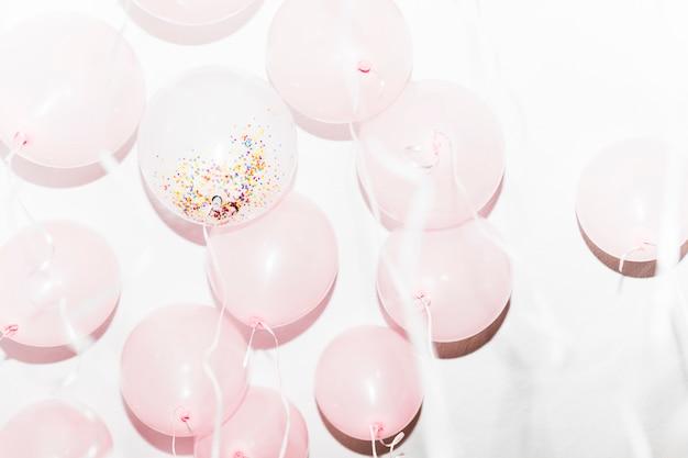Globos de cumpleaños blancos y rosados sobre fondo blanco