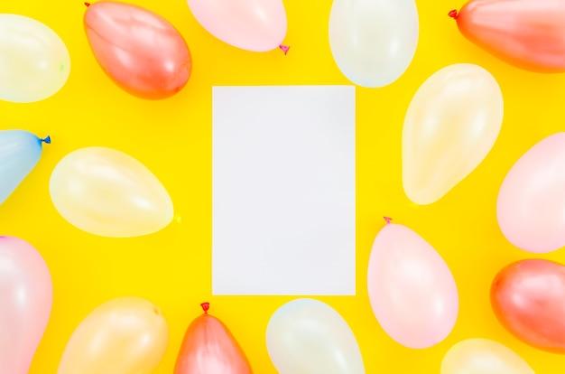 Globos de cumpleaños coloridos con una hoja de papel