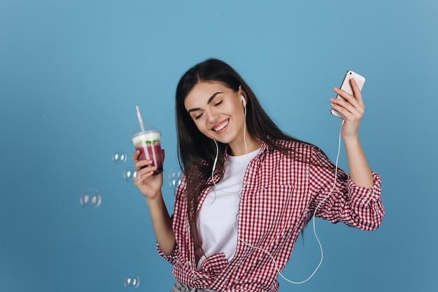 Globos de jabón vuelan alrededor de una niña feliz bebiendo batido de leche y bailando con los auriculares