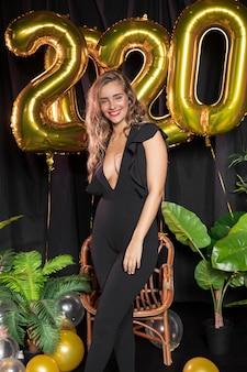 Globos dorados de año nuevo 2020 y hermosa niña