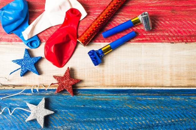 Globos estrellas brillantes cuerno de fiesta y petardo sobre fondo de madera pintado.