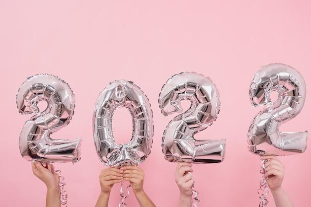 Globos festivos desde los números sobre un fondo rosa
