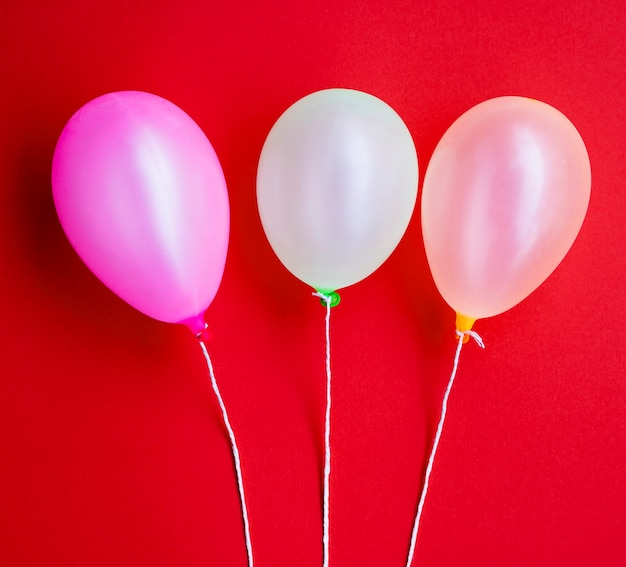 Globos de fiesta de cumpleaños sobre fondo rojo.