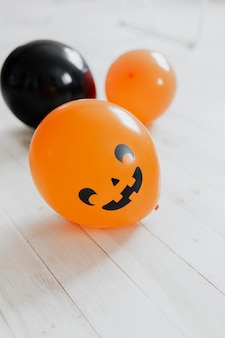 Globos de halloween naranjas y negros en el piso de madera blanca