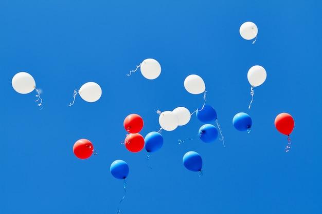 Globos de helio multicolores volando en el cielo azul