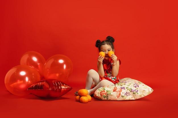 Globos y mandarinas para el estado de ánimo. posando lindo. . niña linda asiática aislada en la pared roja en ropa tradicional. celebración, emociones humanas, vacaciones. copyspace.