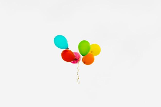 Globos multicolores en cielo nublado