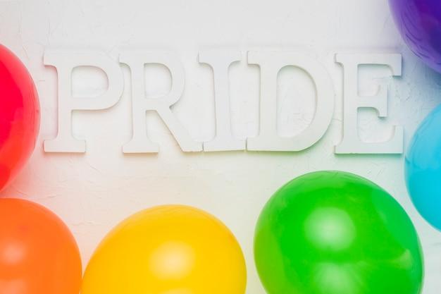 Globos multicolores y palabra orgullo.