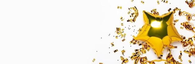 Globos de oro de aire estrella y confeti forma sobre un fondo blanco.