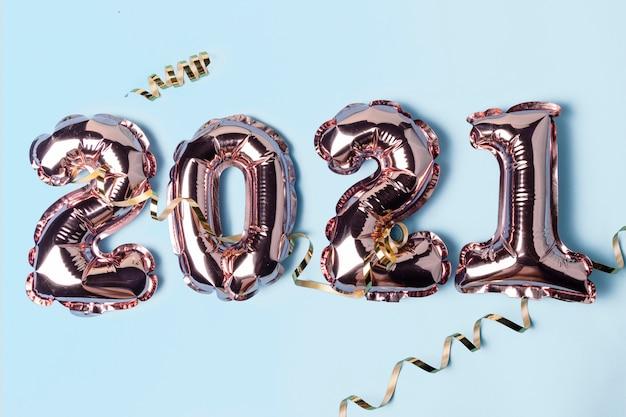 Globos de oro en forma de números 2021 con serpentina sobre superficie azul