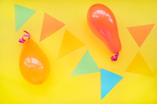 Globos y papel de forma de triángulo sobre fondo amarillo