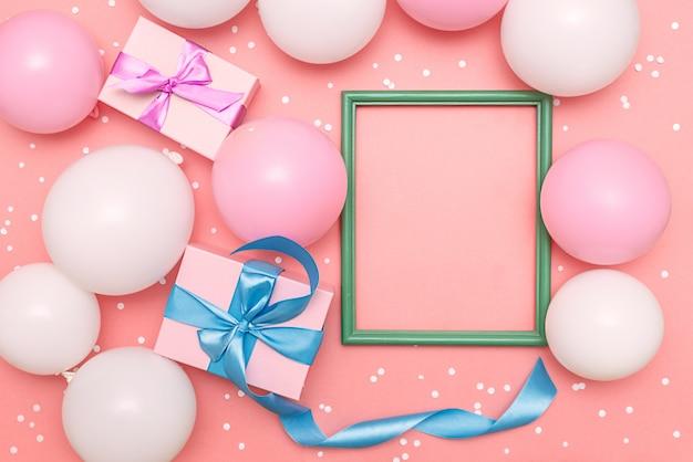 Globos pastel y confeti blanco sobre fondo rosa