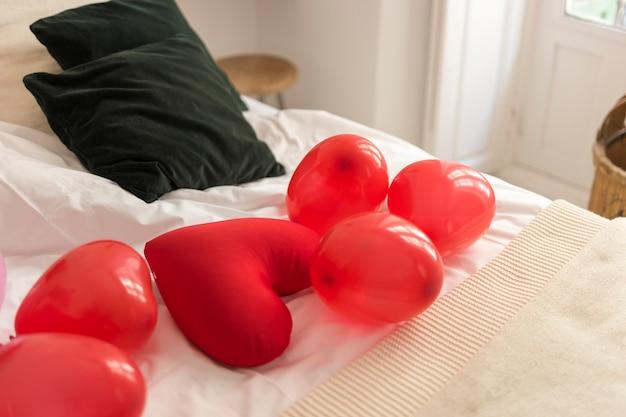Globos rojos y almohada en forma de corazón en la cama