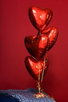 Globos rojos en forma de corazón llenos de helio sobre fondo rojo