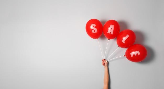 Globos rojos con signo de venta en mano de mujer con espacio de copia para su texto