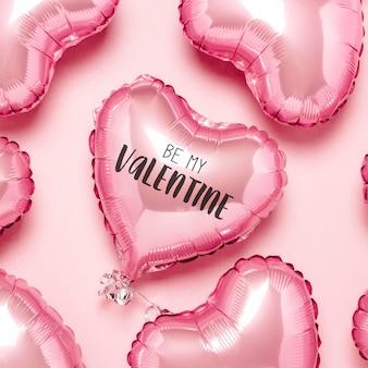 Globos rosados en forma de corazón sobre una superficie rosa. concepto para el día de san valentín
