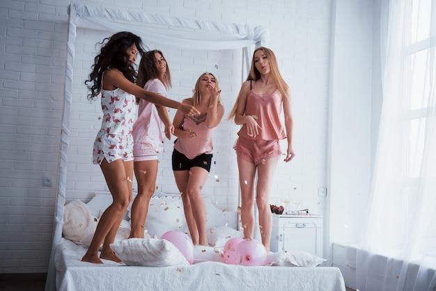 Globos rosados y otras cosas de vacaciones. confeti en el aire. las chicas jóvenes se divierten en la cama blanca en una bonita habitación