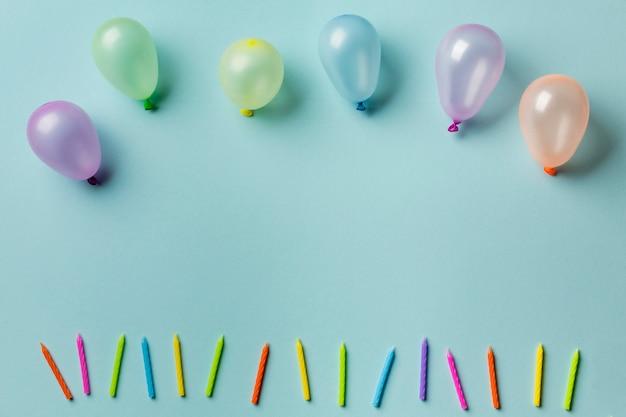 Globos sobre la fila de velas de colores sobre fondo azul