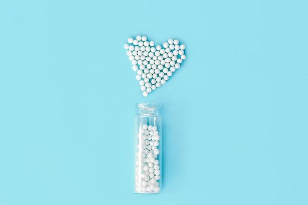 Glóbulos de homeopatía clásica en forma de corazón y botellas de vidrio vintage sobre fondo azul.