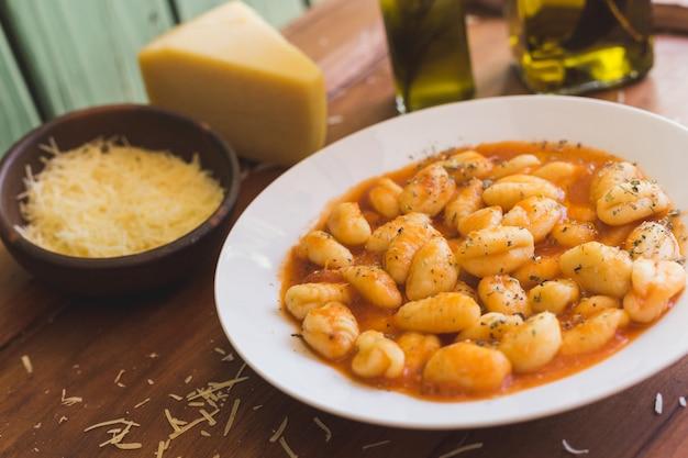 Gnocchi de boloñesa, queso y aceite de oliva sobre una mesa rústica.
