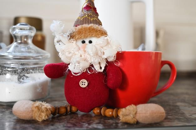 Gnomo de navidad y gran taza de café roja en el fondo