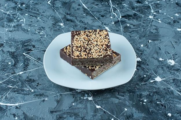 Gofre recubierto de chocolate en un plato, sobre la mesa azul.