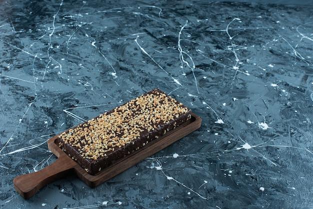 Gofre recubierto de chocolate sobre una placa, sobre la mesa azul.