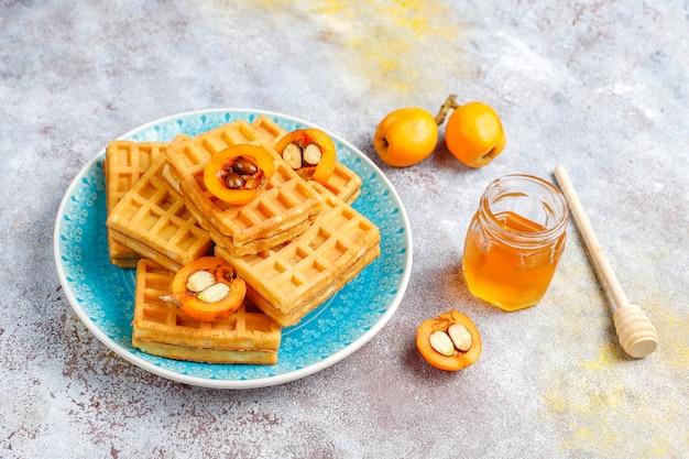 Gofres belgas cuadrados con frutas de níspero y miel.