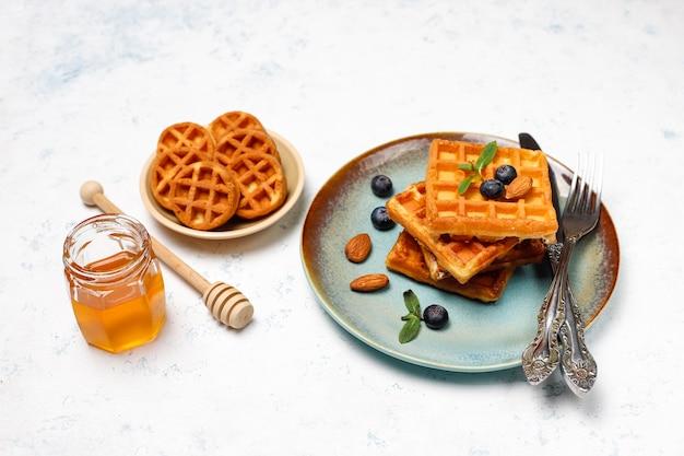 Gofres belgas tradicionales con bayas frescas y miel sobre superficie de hormigón gris.