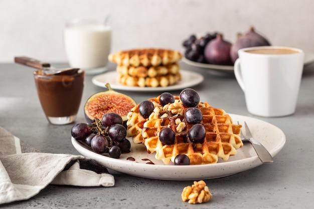 Gofres belgas tradicionales con salsa de caramelo, uvas e higos. acogedor desayuno de otoño o invierno.