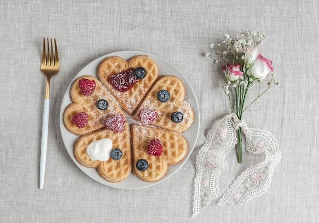 Gofres caseros de corazón belga con salsa de fresas y bayas con flores