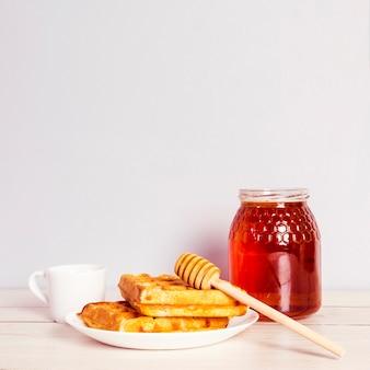 Gofres deliciosos; tarro de miel y café para el desayuno en la mesa de madera