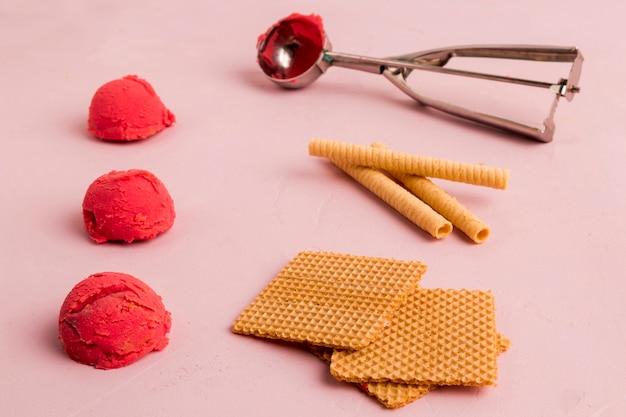 Gofres de helado rojo y cuchara de helado de metal