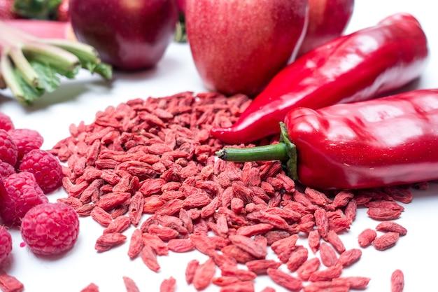 Goji y otras frutas rojas y vegetales sobre un fondo blanco