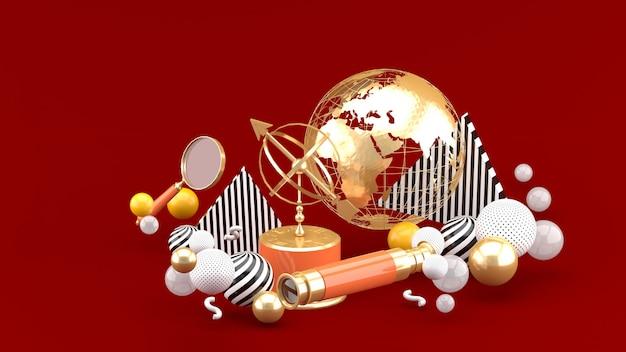 Golden globe, lupa, binoculares y reloj de sol entre bolas de colores en un espacio rojo