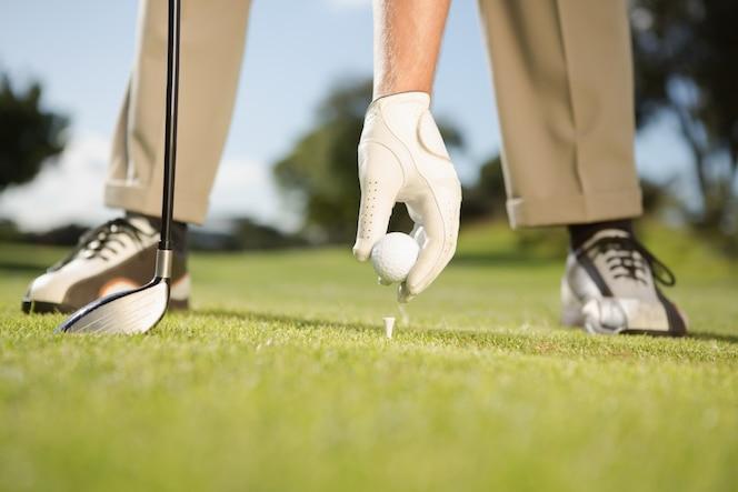 Golfista colocando la pelota de golf en tee
