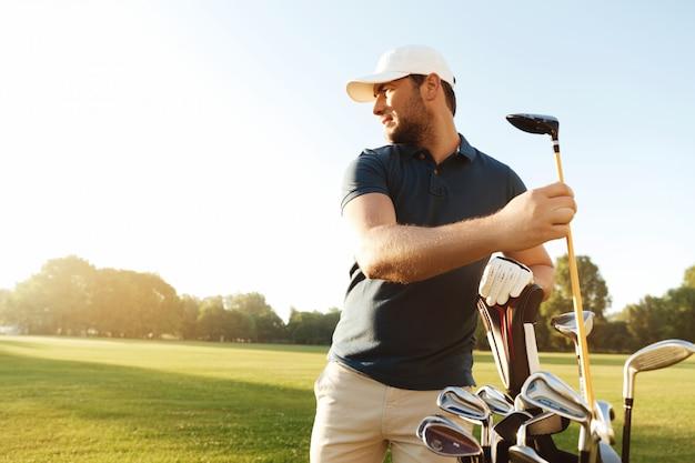Golfista hombre sacando el club de golf de una bolsa