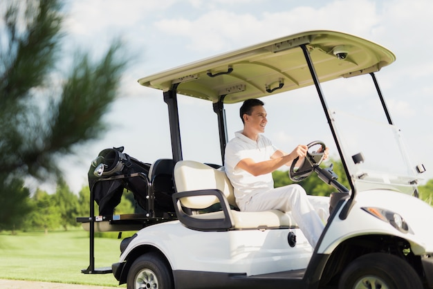 El golfista joven conduce la diversión del lujo del coche del golf.