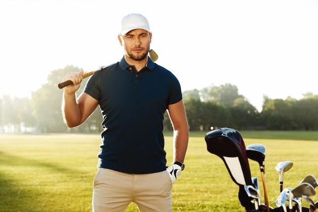 Golfista masculino confiado hermoso que se coloca con el club de golf