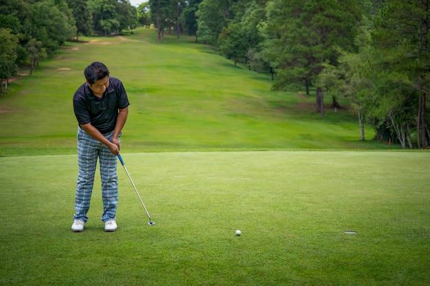 Golfista poniendo la pelota de golf en el hoyo en campo verde
